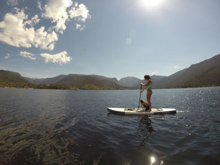 Side view of woman paddleboarding and dog in grand lake against sky