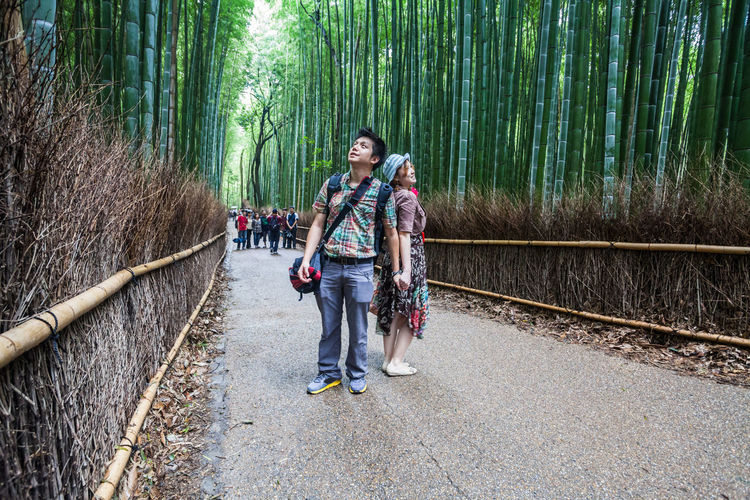 Smiling couple standing on pathway amidst bamboos at arashiyama