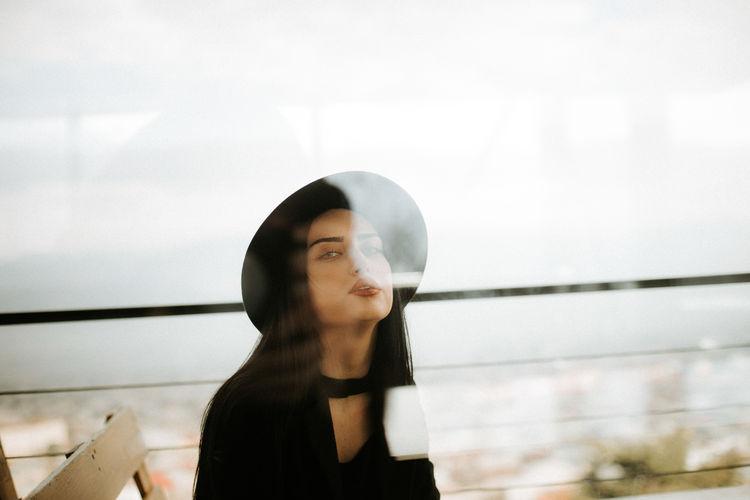 Portrait Of Woman Wearing Hat Seen Through Window