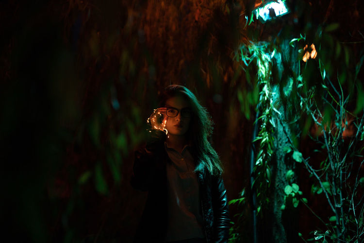 Portrait of young woman holding illuminated string lights at night