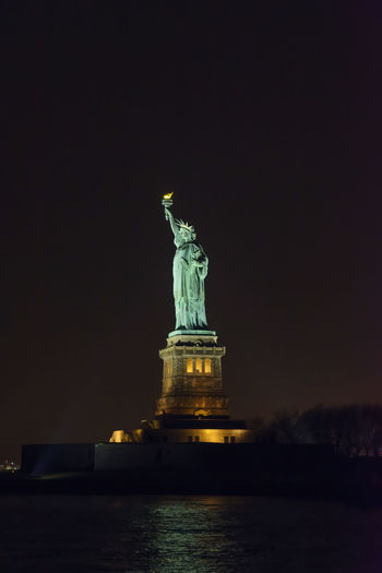 Statue of liberty against sky at night