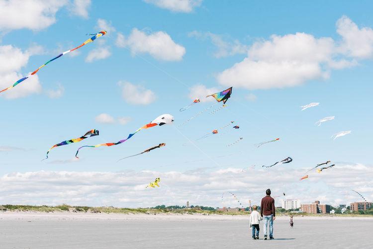 Rear view of men flying kite against sky