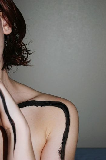 Midsection of shirtless woman with painted body