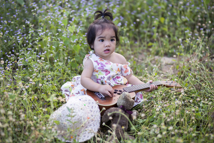 Cute baby girl sitting on field