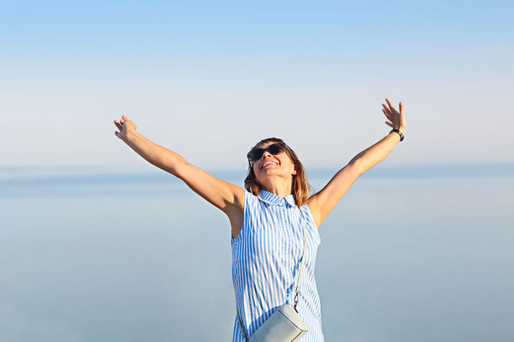 Cheerful woman with arms raised standing against sea