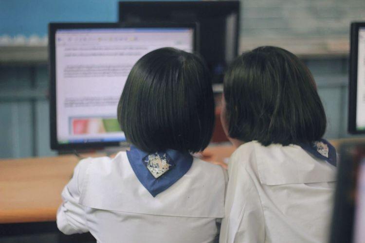 Rear view of two women in laptop