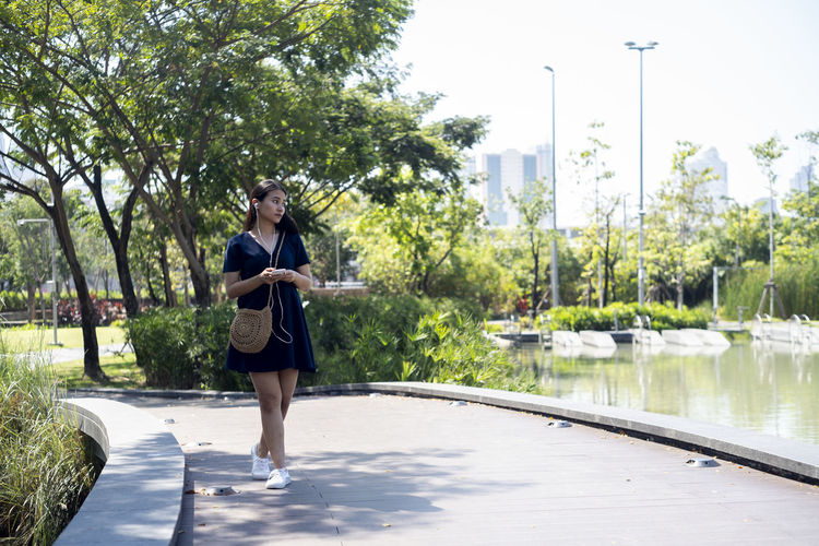 Full length of young woman standing on riverbank