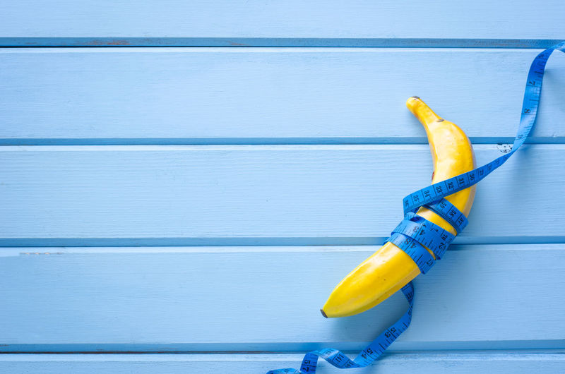 Directly above shot of banana and tape measure on blue wooden table