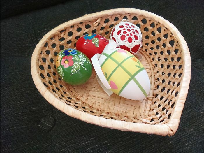 High angle view of multi colored easter eggs in heart shape wicker basket on table