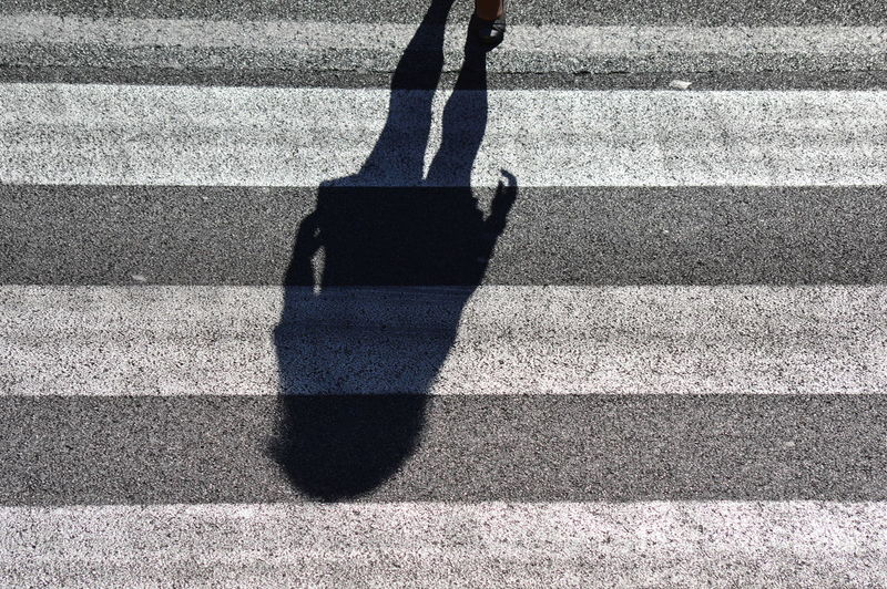 Shadow of woman on zebra crossing in city during sunny day