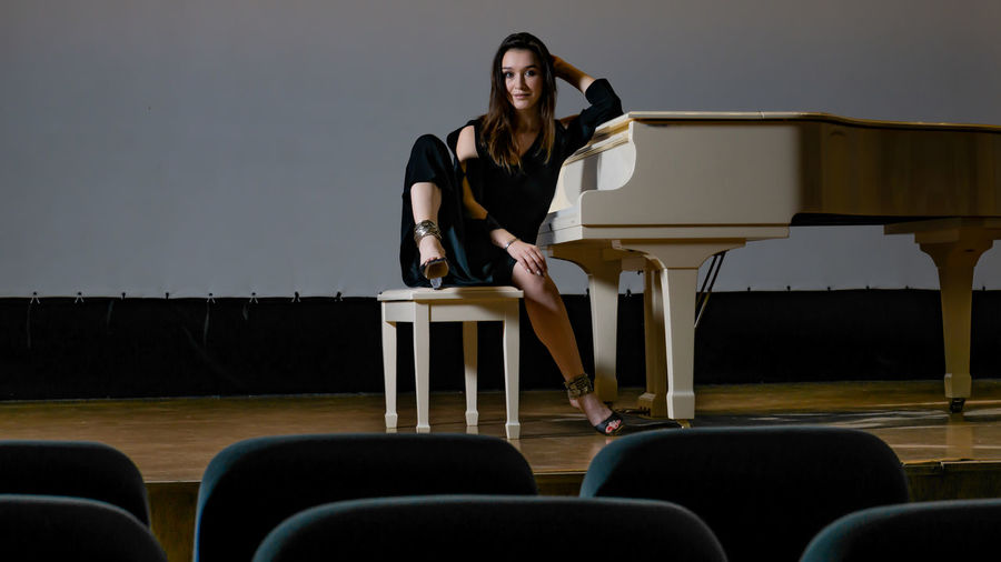 Woman sitting on chair by piano against wall