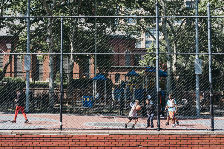 Teenagers play basketball on a public court in Brooklyn, New York, on a bright summer day. Tourism Travel United States USA New York City New York Sport Fence Playing Day People Outdoors Playing Field Healthy Lifestyle Kids Teenagers  Basketball Brooklyn Basketball Court Public Outside Youth Youth Culture African American Competition