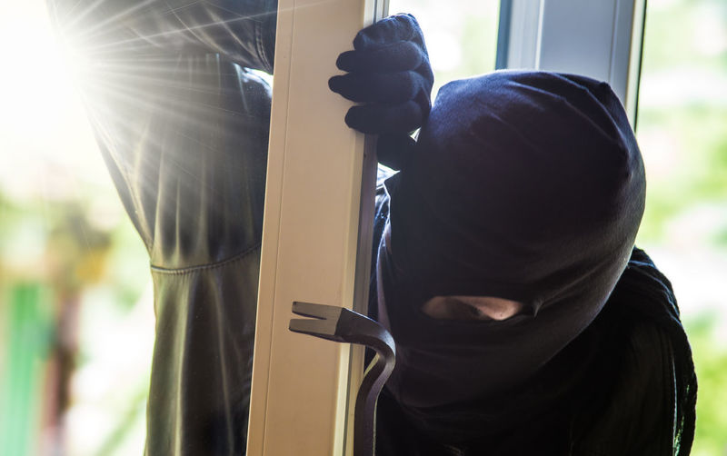 a burglar breaks into a house during the day Crowbar Burglar Burglary Close-up Criminal Danger Dangerous Day Daylight Men One Person Outdoors People Real People Safety Steal Sunlight Thief Window