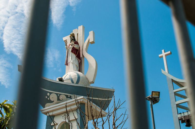 Low angle view of jesus christ against sky seen through fence