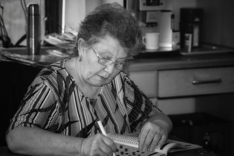 Senior woman writing in newspaper while sitting at home