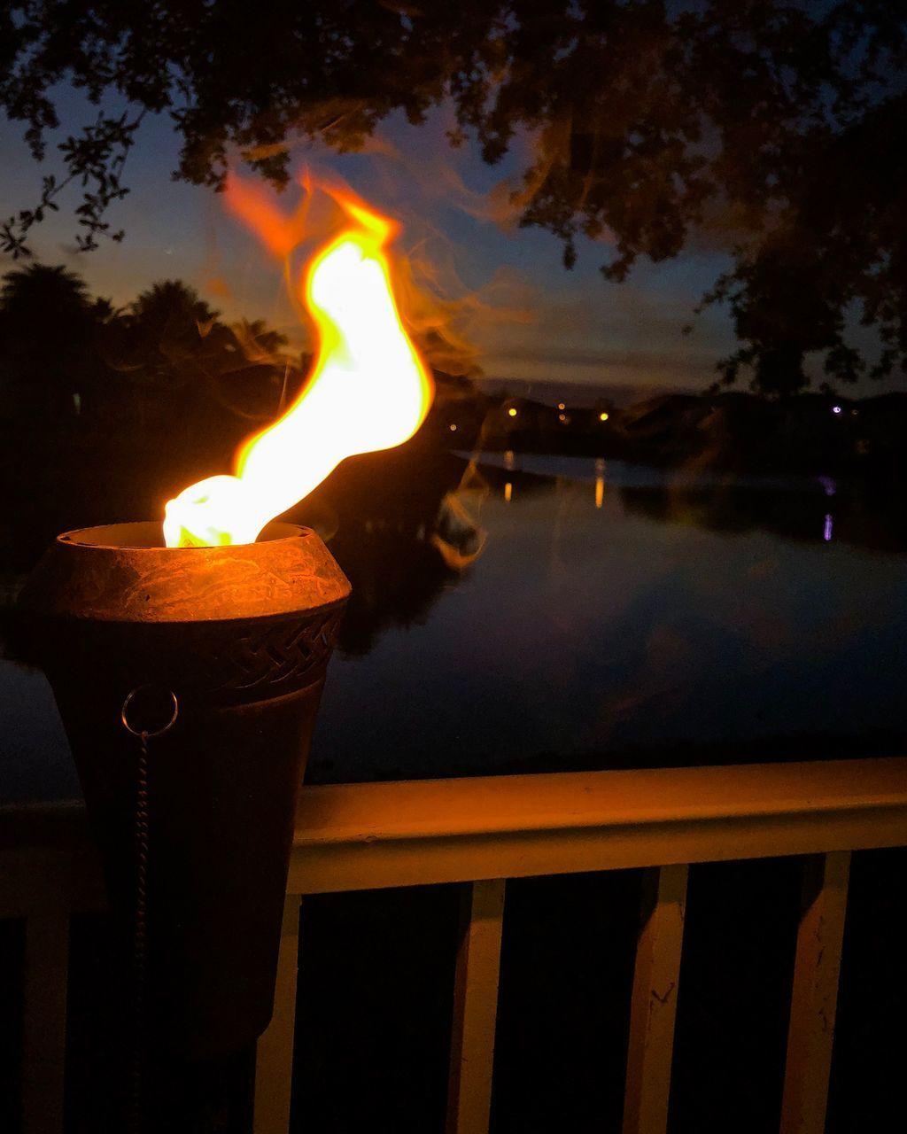 CLOSE-UP OF BURNING CANDLE AGAINST RAILING AT SUNSET