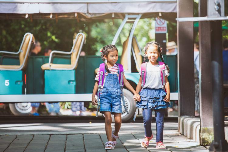 Schoolgirls Holding Hands While Walking On Street