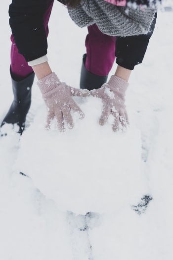 Low section of woman standing on snow covered field