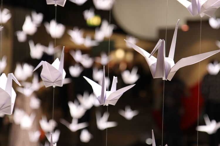 Close-up of paper cranes hanging on strings