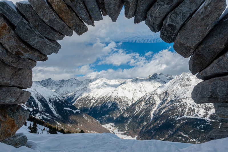 Scenic view of snowcapped mountains seen through rock formation against sky