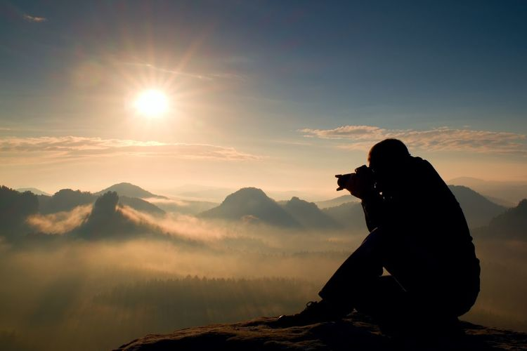 Happy photo enthusiast is enjoying fantastic miracle of nature on cliff on rock.