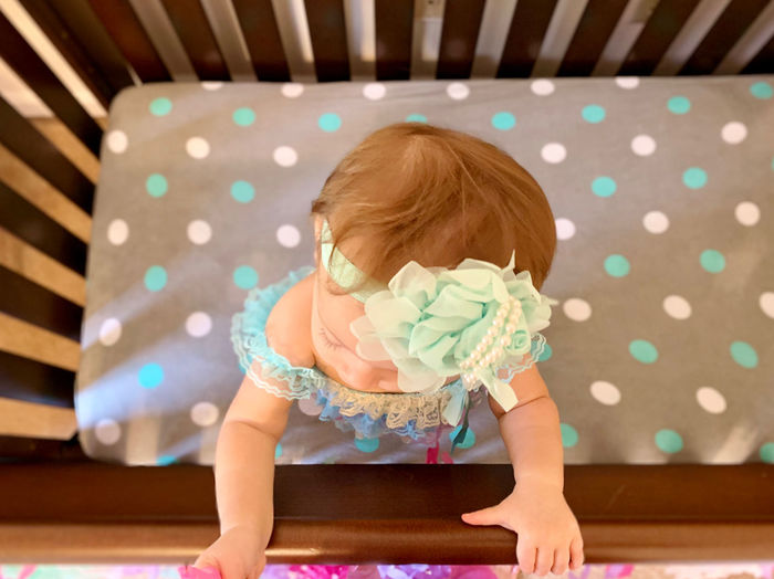 High angle view of baby girl standing in crib