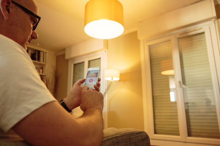 App Domestic Life Home Home Automation Internet Of Things Light Mobile Phone Close-up Communication Control Holding Human Hand Indoors  Internetofthings One Person People Phone Real People Smart Home Smart Phone Technology Wireless Technology