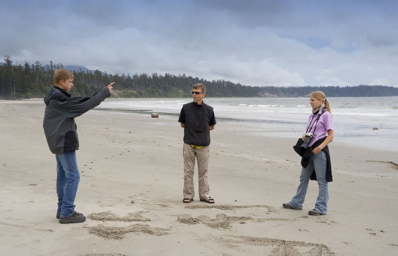 Father and daughter looking at boy standing at pacific rim national park reserve beach