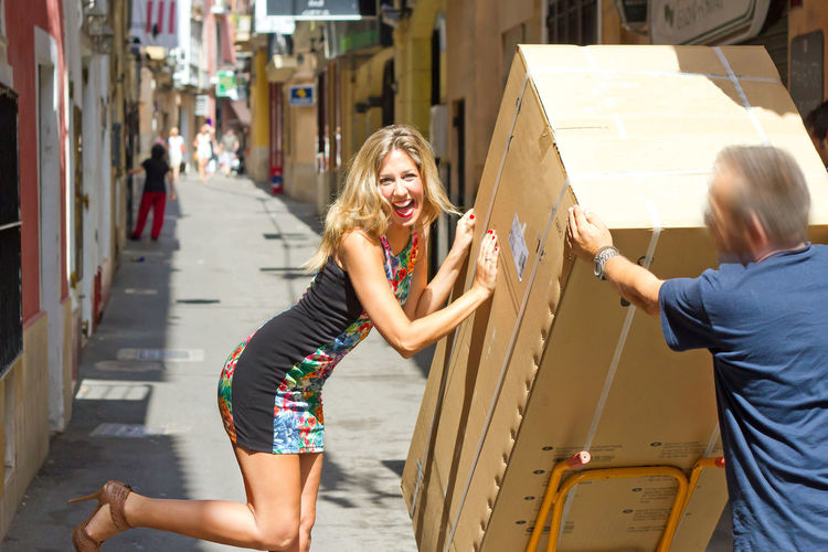 Portrait Of Happy Woman With Man Holding Cardboard Box In Alley