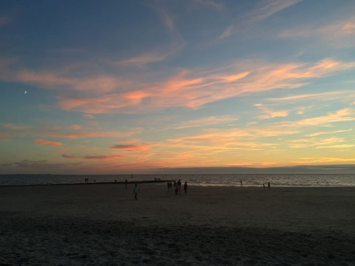 Scenic view of beach against dramatic sky during sunset
