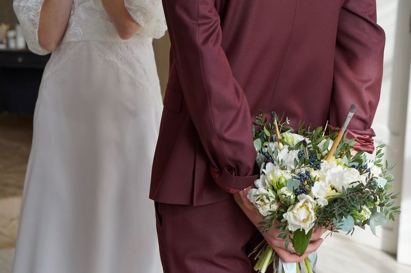 Midsection of bridegroom holding bouquet standing by bride