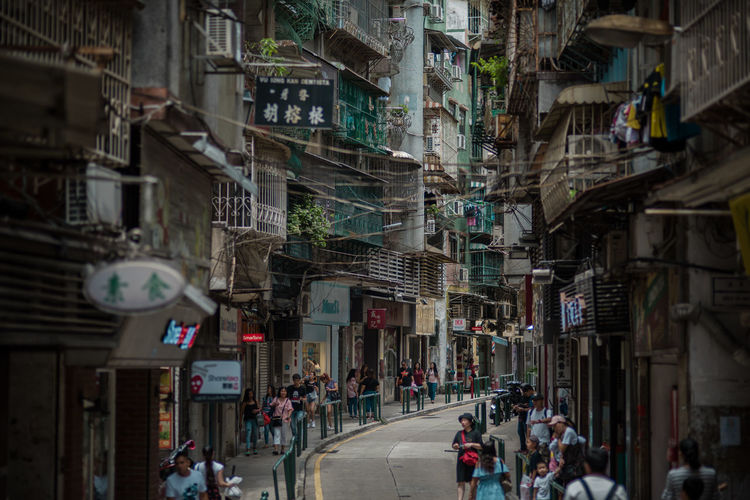 People in alley amidst buildings in city
