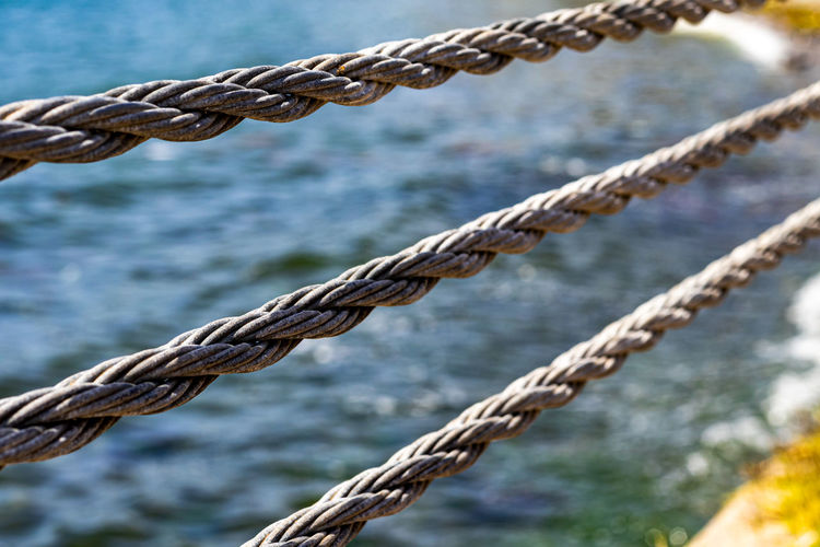 Close up steel rope at beach and sea. grey cord.