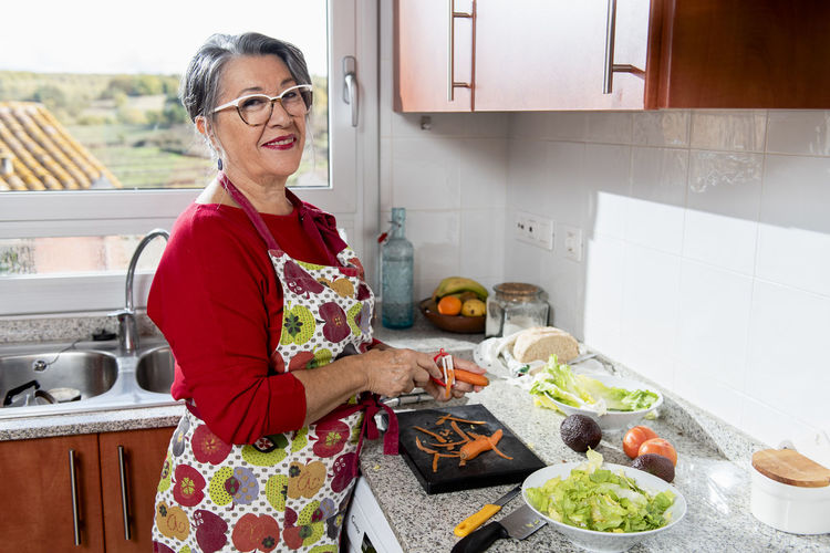 Midsection of woman standing in kitchen at home
