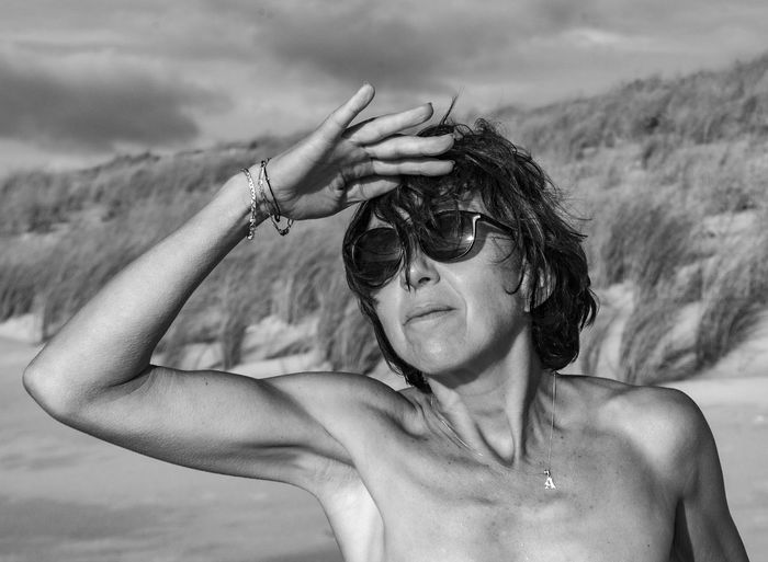 Shirtless woman wearing sunglasses shielding eyes at beach