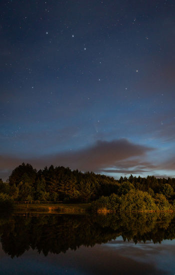 Scenic view of lake against starry sky at night
