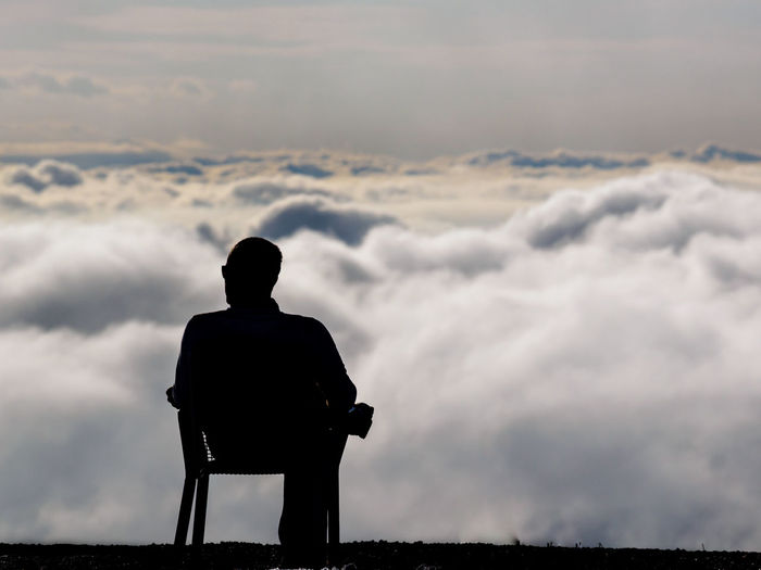 Rear view of silhouette man sitting against sky