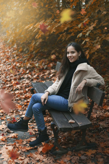 Portrait of smiling young woman sitting on autumn leaves