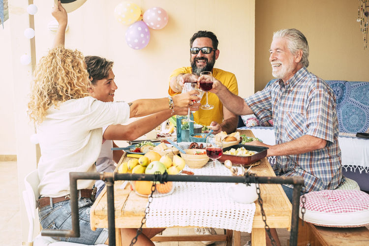 Family toasting with big smiles. enjoying bbq outdoors in the terrace. Wooden table. Bright light and balloons on background. Focus on man with black hair 50 Years  70 Years Adult Background Balloons BBQ Beard Bright Casual Caucasian Checkered Cuisine Curly Hair Domestic Dots Drink Drinking Eat Eating Emotion Enjoying Freshness Friendship Fruit Grandfather Light Love Lunch Meal Natural Outdoor Parents People Positive Vibes Potatoes Recycled Red Rustic Senior Smiling Son Sunlight Table Teenager Terrace Field Together Vintage Wineglass Wood Wooden