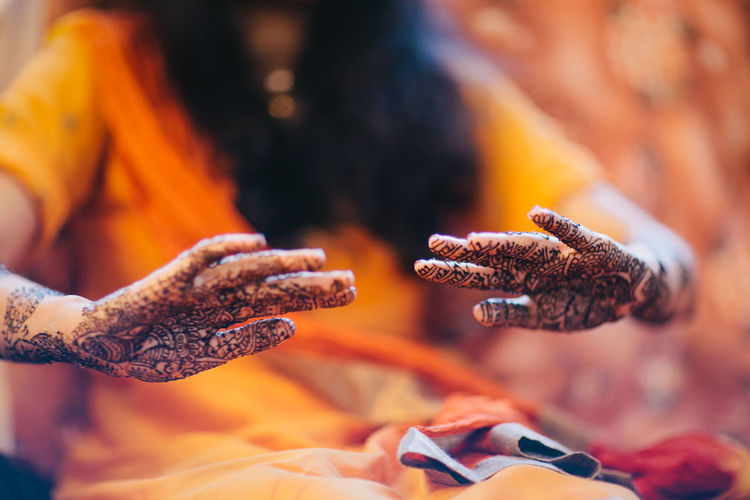 Midsection of woman with henna tattoo on hand sitting at home