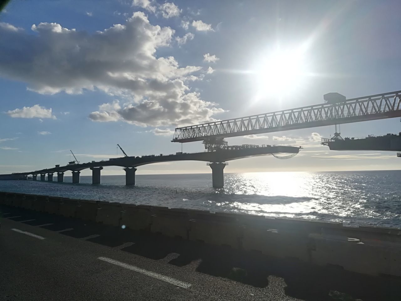 sun, lens flare, water, sunlight, sea, bridge - man made structure, sky, sunset, nature, built structure, outdoors, connection, scenics, architecture, silhouette, tranquility, travel destinations, beauty in nature, no people, cloud - sky, horizon over water, day