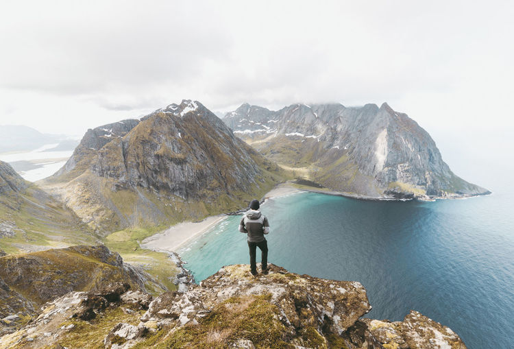 Rear view of man standing on cliff by sea at lofoten archipelago