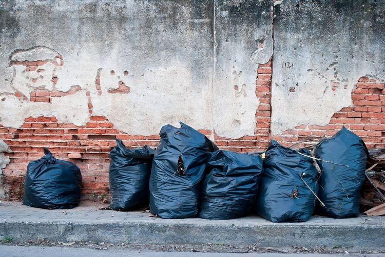 Garbage in plastics on sidewalk against wall