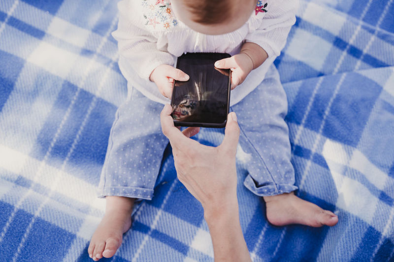 Cropped hand of woman giving phone to baby girl