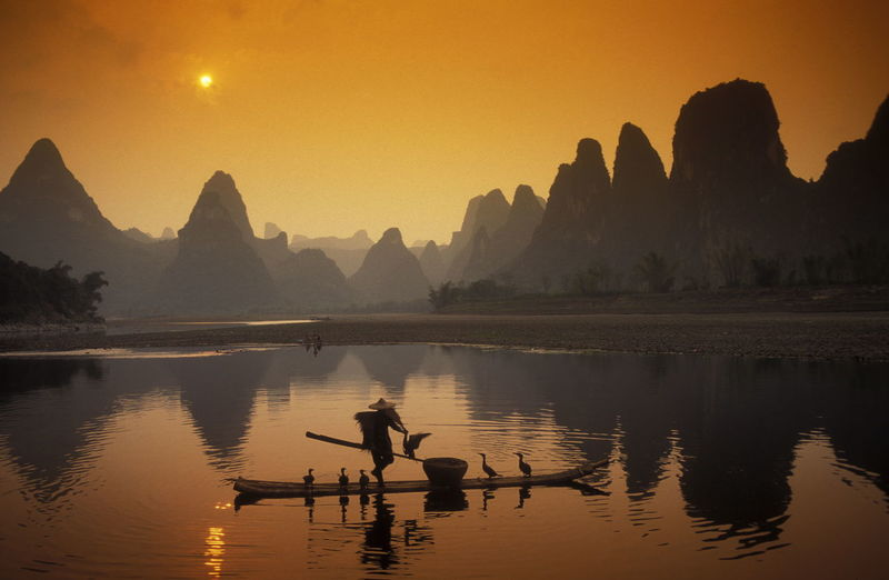 Man Sailing Boat With Birds In River Against Mountains