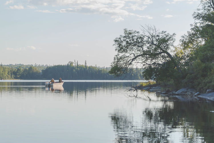 View of man sitting in lake against sky