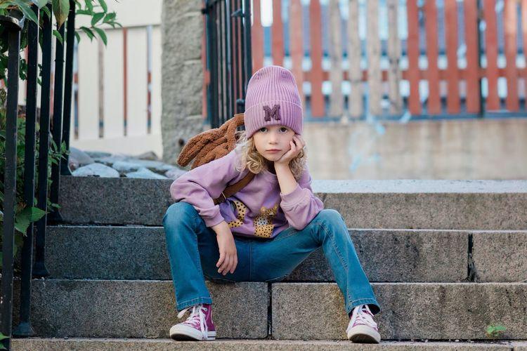 Full length portrait of girl sitting on staircase
