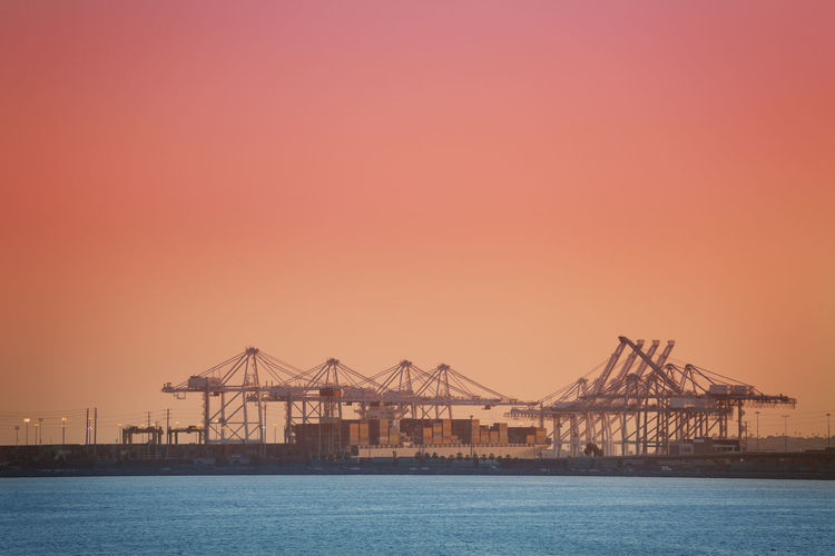 Cranes in sea against clear sky during sunset