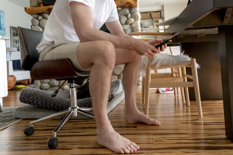 Low section of man sitting on chair at home