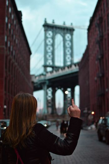 DUMBO DUMBO, Brooklyn Manhattan Bridge Brooklyn Middle Finger Middle Finger Up Built Structure Architecture Building Exterior Real People Travel Destinations Outdoors Headshot Streetphotography Street Photography Rsa_streetview NYC NYC Street Photography NYC Photography NYC Street New York City One Person Women Rear View Human Hand